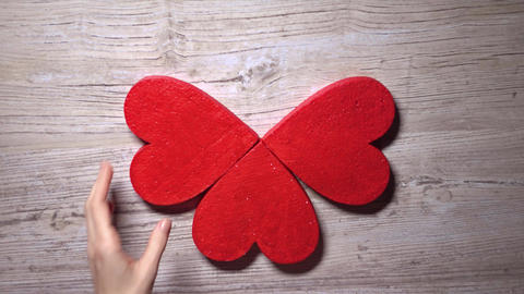 Girl taking four red hearts from a wooden table, top view. Care, love, Valentine Footage