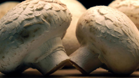 Uncooked mushrooms on wooden cutting board. 4K long pan shot Image