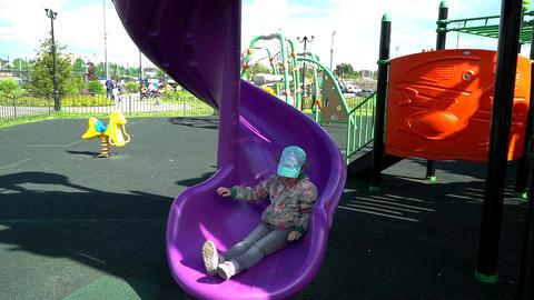 A little girl slides down the slide Live Action