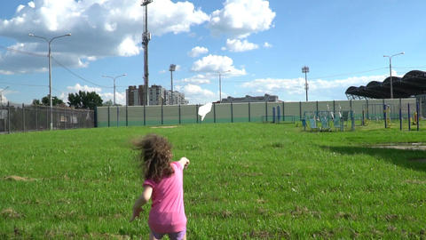 Little European girl starts paper plane in the Park Footage