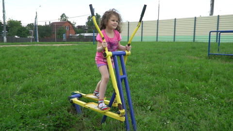 The little girl is at the gym under the open sky Archivo