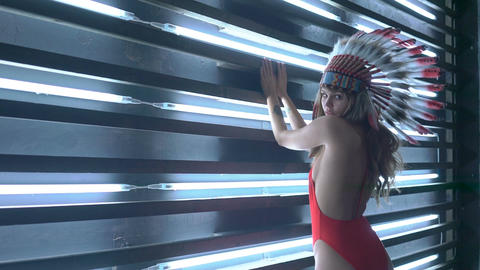 Sexy model in red swimsuit with native American headdress posing over neon lamps Footage