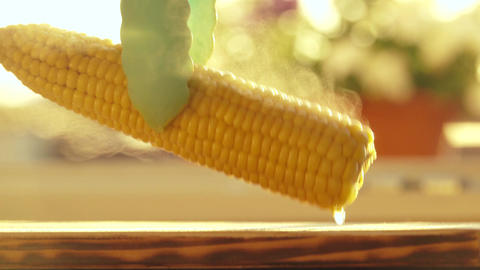 Female hand placing a piece of butter on hot corn Footage