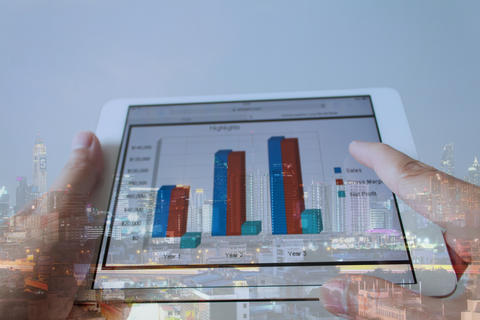 Businessman hand touching screen of tablet computer with market graph on Foto