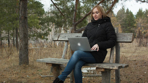 girl with a laptop in the autumn forest working Footage