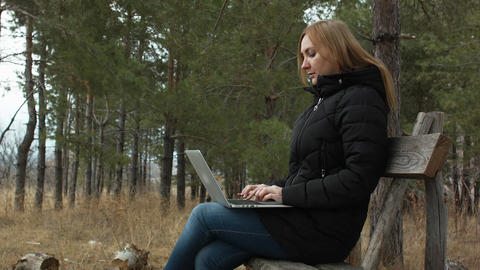girl with laptop on a park bench in a forest on a background of trees. work in Footage