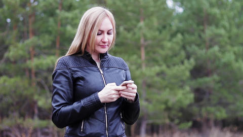 girl blonde in a black jacket enjoys a smartphone on a tree background Footage