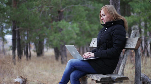 girl on a bench in an autumn park enjoys a laptop. dials text, surf internet Footage