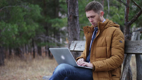 the guy in a tie and jacket is sitting with a laptop on a bench in an autumn Footage