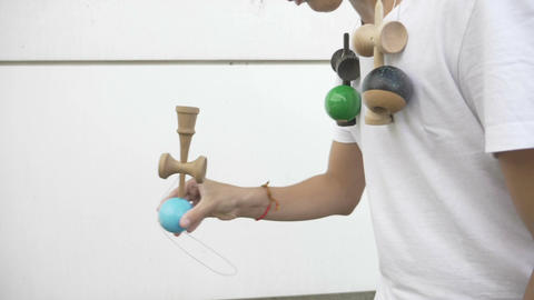 Closeup of confident boy playing with kendama toy and practicing balance border Footage