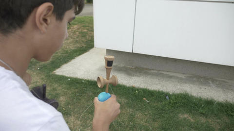 Closeup of focused kid balancing kendama ball on spike in slow motion Footage