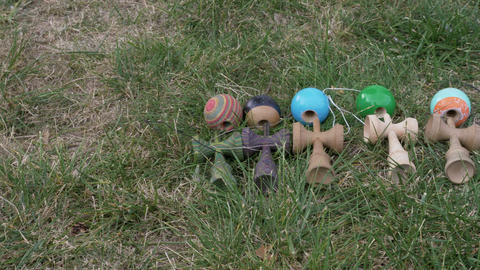 Collection of kendama toys sitting down on the grass Live Action
