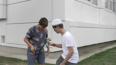 Two boys playing with one kendama outdoor Footage