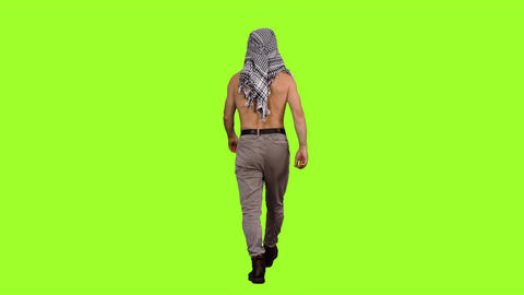 Back view of shirtless male tourist in arabic scarf walks on green background Footage