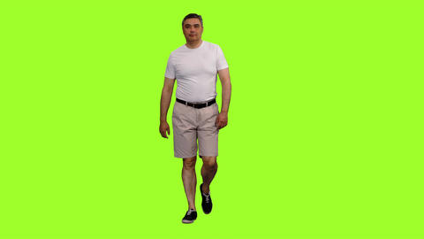 Adult man in shorts and white t-shirt walks on green screen background Footage