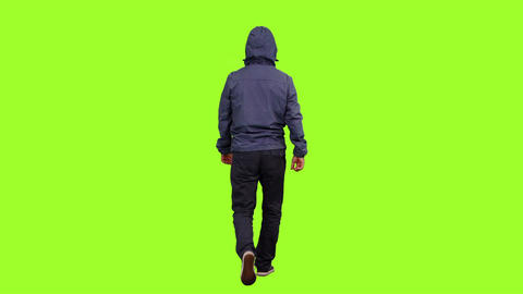 Back view of a hooded man walks on green screen background, Chroma key Live Action