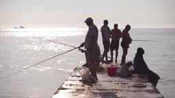 fishermen fish on the pier at sunrise Footage