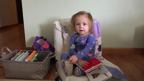 Baby holding up book to read sitting on tiny sized chair in pajamas Footage