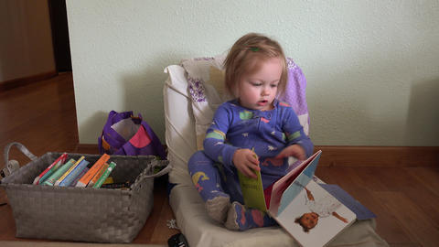 Baby holding up book to read sitting on tiny sized chair... Stock Video Footage