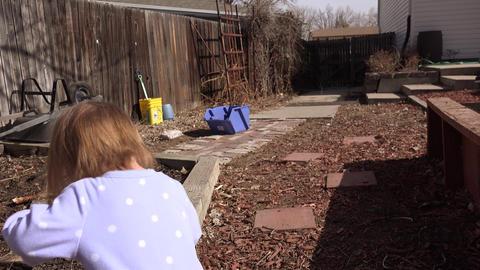 Baby walking outside backyard garden landscaped area smiles Footage