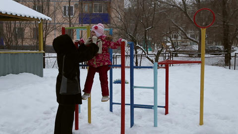Girl playing on the sports playground in winter Footage