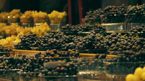 Boxes with white and black grape at fruit stall on the marketplace Footage