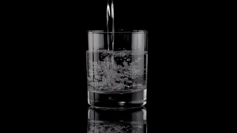 Filling a glass of water on black Footage