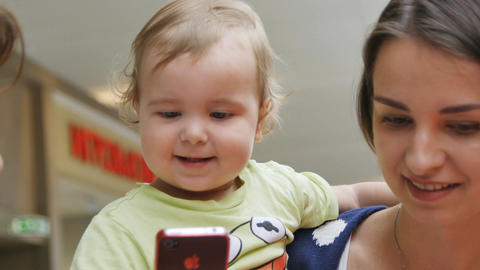 Closeup Baby Looks at Mommy Smartphone in Shopping Mall Footage