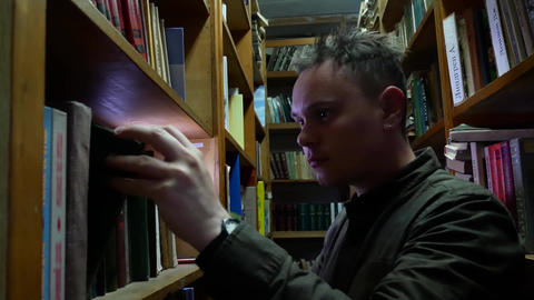 Man picking out book in library in dark Footage