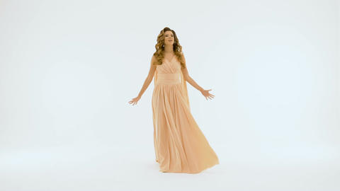 A singer with beautiful long hair, in a long beige dress singing against a white Footage