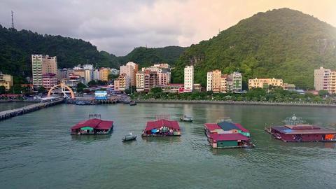 Flycam Shows Floating Restaurants in Ocean Bay against Town Footage
