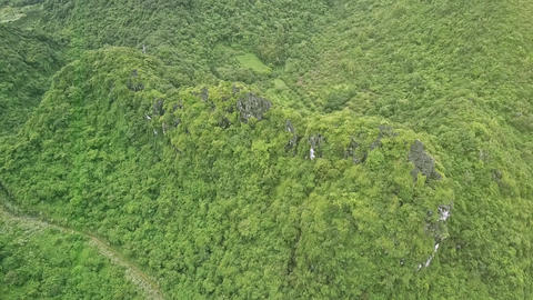 Flycam Descends Slowly to Green Hill with Road at Foot Live影片