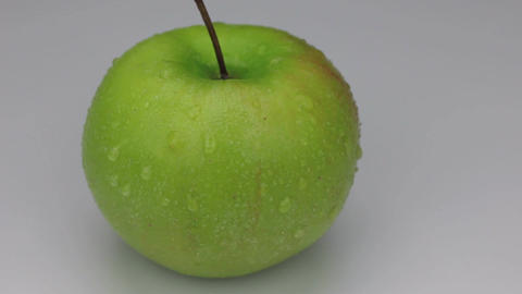 Rotation of a green apple in drops of dew on a white background Footage