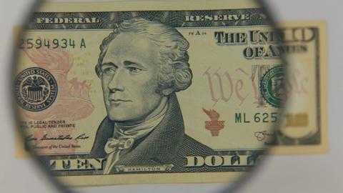 Approaching using a magnifying glass ten dollar bill Footage