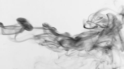 Stream of black smoke turning into smoke puffs on a white background Footage