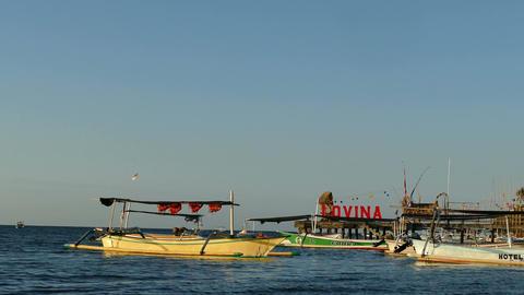 Boats at Lovina beach with sign at sunset, Bali, Indonesia Live Action