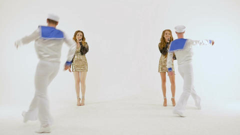 Four professional actors singing and dancing in the studio on a white background Footage