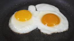 Two eggs are fried in a frying pan in oil Footage