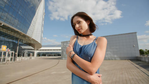 Sad young woman posing with industrial background and glass buildings Footage