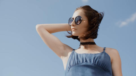 Young girl portrait posing in sunglasses with blue sky background Footage