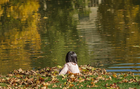 Child Plays With Leaves On A Pond In Autumn Foto