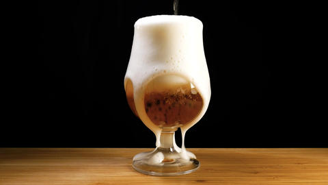 A craft beer is poured into a glass and foamed over Live Action