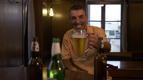 Drunk man laughing and drinking beer alone at a pub Live Action