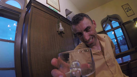 Drunk man looking at his alcohol glass and laughing and drinking Live Action
