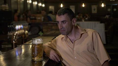 Drunk guy drinking beer alone at the bar in a pub and falling asleep on the bar Footage