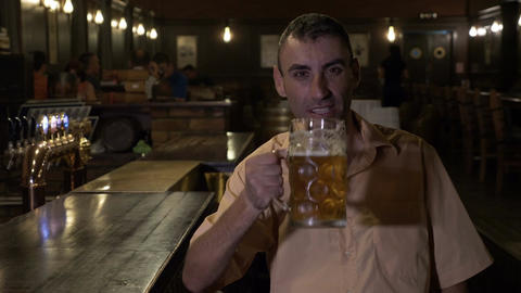 Laughing cheerful man having a beer and watching TV at the bar Footage