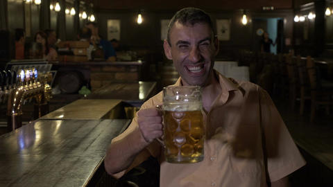 Smiling cheerful man drinks beer at the bar and cheers looking at camera Live Action