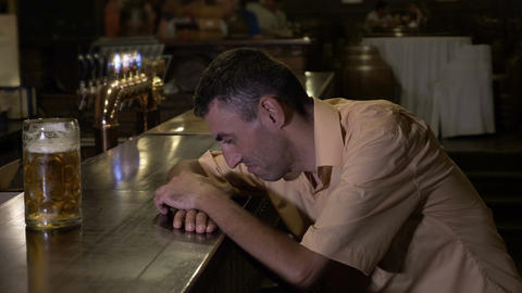 Too drunk guy holding his head on the bar cannot reach his glass Live Action
