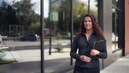 Attractive business woman walks near office building with documents in hands Filmmaterial