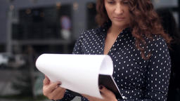 Young business woman looking at documents with a serious look near office Footage